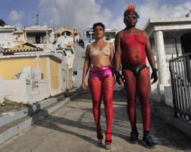 Annabel Guérédrat and Henri Tauliaut stand defiantly hand-in-hand in the middle of a street, both wearing red mesh clothing and looking directly ahead.