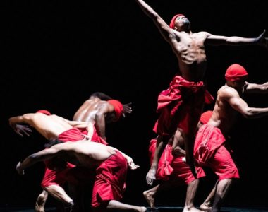 A group of Black dancers in red trousers and headwear, grouped together crouching and leaping