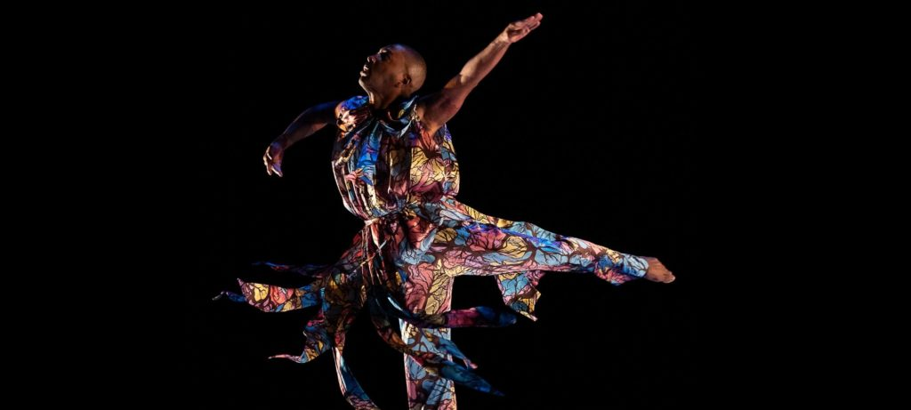 Black dancer Kyle Abraham is leaping with arms spread and one leg kicked out behind him. He wears a colourful costume with loose tassels that flow out as he moves.