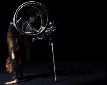 Dancer Alice Sheppard, balances on her hands, arms straight, and on a pair of silver crutches, lifting her lower body and wheelchair high. Alice's head is tucked and her short curly hair peaks out from behind her strong arms. She is wearing a shimmery gold bodysuit. She is set against a black background and light reflects off her costume, chair, and crutches. Photo by Mengwen Cao.