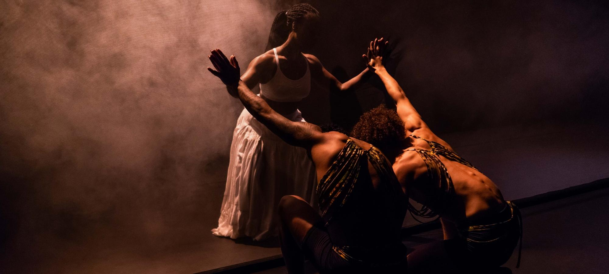 A Black woman in a white dress holds out her hands, palm to palm with two men crouched down before her