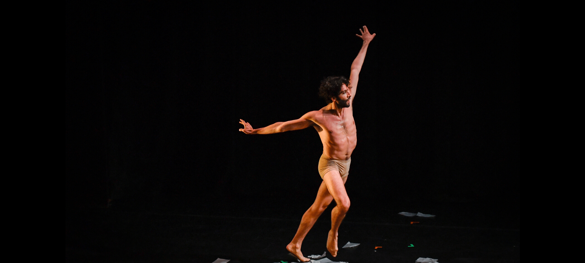 A dancer wearing light coloured shorts stands amidst book pages o the floor, stretching his arms up