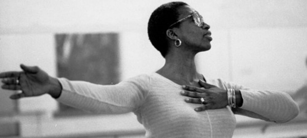 Angela Bowen, a Black woman with short hair, wears a white top and stands with one arm extended, and her other hand on her heart