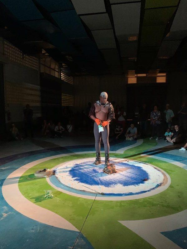 Artist Henri Tauliant stands in a blue circle