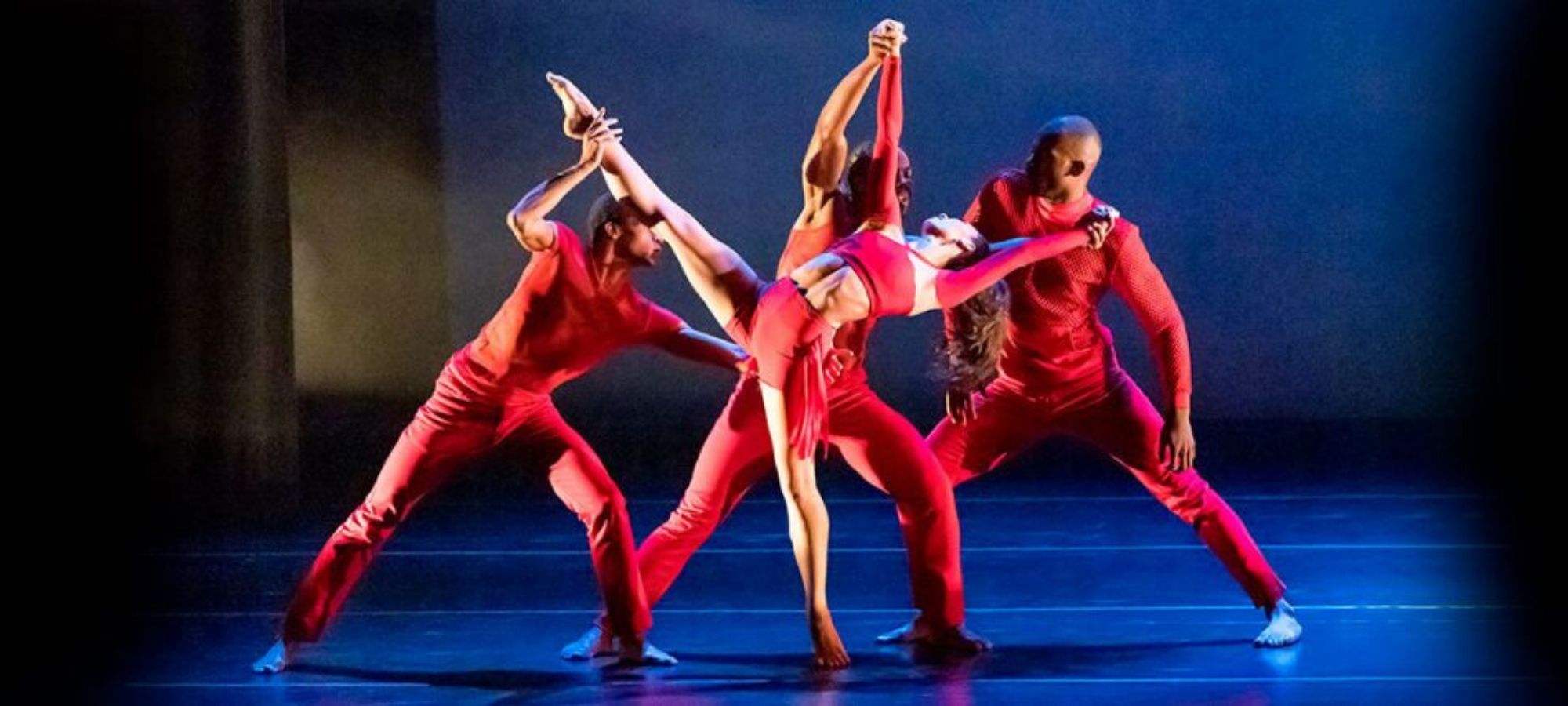 A female dancer in red leans in to a standing split supported by three men in red