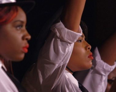 Three Black teenager girls stand in a line, all wear white shirts and defiant expressions with their fists raised in the air