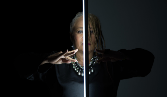 Choreographer and dancer L'Antoinette Stines looks straights ahead into the camera. A light bar illuminates the right side of her face, while casting a shadow on the left side