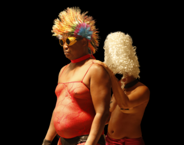 Artist Annabel Guérédrat walks behind artist Henri Tauliaut. Henri leads Annabel, her hand resting on his shoulders. Henri is wearing a rainbow mohawk wig and a red mesh vest and yellow welders goggles. Annabel is a wearing a Marie Antoinette wig