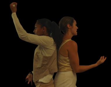 Two dancers with their backs against each other in mid-movement