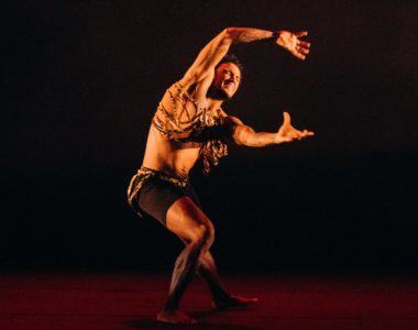 Dancer Wolman Michelle Luciano from Tabanka Dance Ensemble is in mid-movement with his arms arched forward
