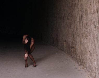 Dancer Yinka Esi Graves is in mid-movement, with her head down and arms covering her face