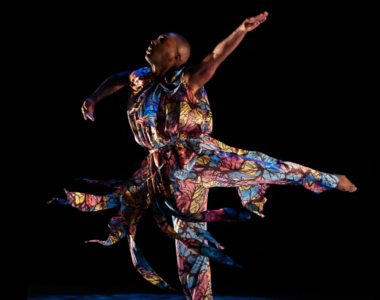 On a black background, dancer Kyle Abraham is looking up, balanced on one leg, his other leg extended behind him. His arms are held out to the side