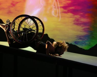 On a multicoloured background, dancer Alice Sheppard is launching forward down a ramp, balancing on her hands lifting her wheelchair high