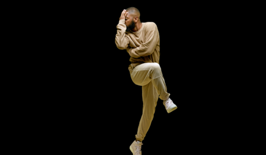 Dancer Kyle Abraham is mid-movement, balanced on one foot, with one arm wrapped around his chest and the other covering his face