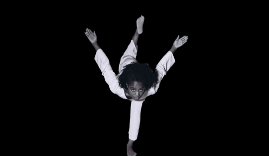 Dancer S. Ama Wray is looking forward, balanced on one foot, with both arms launching behind her