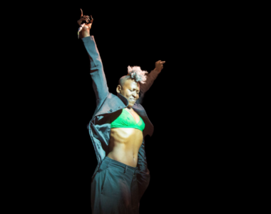 Practitioner Nora Chipaumire is mid-movement holding a microphone with both her arms raised up