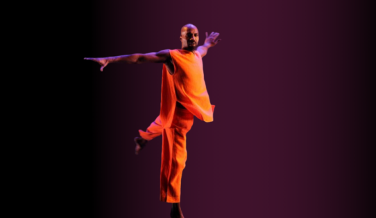 Choreographer and dancer Ronald K Brown is mid movement, balanced on one leg and arms held out to the side